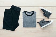 T-shirt avec le pantalon et les chaussures sur le fond en bois Photos libres de droits
