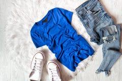 T-shirt bleu, jeans déchirés et espadrilles blanches Concept à la mode sur la fourrure blanche Photographie stock