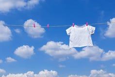T-shirt branco que pendura na linha de roupa Imagem de Stock