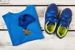 T-shirt, chaussures de sport et médaille Photographie stock libre de droits