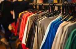 T-shirt de mode accrochant sur le support en métal à l'avant le magasin à vendre photo libre de droits