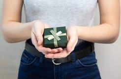 T-shirt de port attrayant et jeans de jeune fille tenant la petite case avec un cadeau images stock
