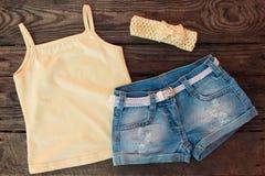 T-Shirt, Denimkurze hosen, Stirnband auf hölzernem Hintergrund Stockfotografie