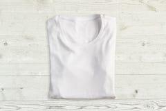 T-shirt dobrado branco na textura de madeira fotografia de stock royalty free