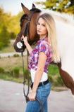 T-shirt e calças de brim vestindo do vintage da jovem senhora bonita que montam a Imagem de Stock