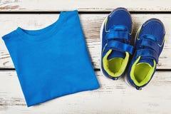 T-shirt en tennisschoenen op hout royalty-vrije stock foto