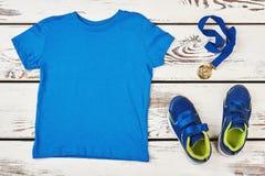 T-shirt, espadrilles et médaille Photographie stock