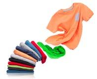 T-Shirt fliegt aus einem Stapel mit Kleidung auf weißem Hintergrund heraus lizenzfreie stockbilder