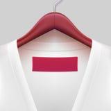 T-Shirt mit dem Aufkleber, der an einem Aufhänger hängt Lizenzfreie Stockfotos