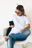 T-shirt mockup on model. Woman wearing blanc t-shirt, jeans and sneakers sitting on chair and playing with black kitten, toned photo, front tshirt mockup on stock photos
