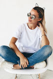 T-shirt mockup on model. Woman wearing blanc t-shirt, jeans and sneakers sitting on chair, toned photo, front tshirt mockup on model, hipster style royalty free stock photos