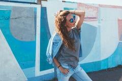 T-shirt modèle et lunettes de soleil simples de port posant au-dessus de la rue wal Photos libres de droits