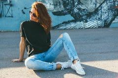 T-shirt modèle et lunettes de soleil simples de port posant au-dessus de la rue wal Photo stock