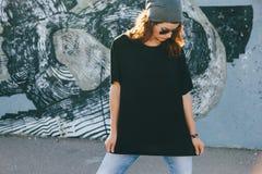 T-shirt modèle et lunettes de soleil simples de port posant au-dessus de la rue wal images stock