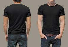 T-shirt noir sur un calibre de jeune homme Photographie stock libre de droits
