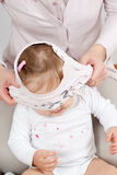T-shirt over babys head. Mother dressing up a t-shirt over babys head Royalty Free Stock Photos