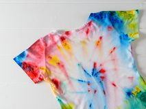 T-shirt painted in tie dye style on a white wooden table. White clothes painted by hand royalty free stock images