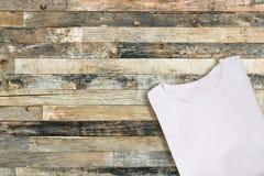 T-shirt plié blanc de blanc sur le fond en bois photographie stock