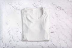 T-shirt plié blanc sur le fond de marbre Configuration plate Vue supérieure image stock