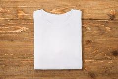 T-shirt plié blanc sur le fond en bois de mur Configuration plate image libre de droits