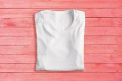 T-shirt plié blanc sur le fond rose photographie stock