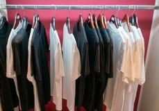 T-shirt preto e branco que pendura na barra de madeira a do gancho e de metal imagens de stock