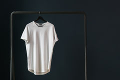 T-shirt with short sleeves on a hanger against the background of a dark wall. In the left part of the image white empty T-shirt with short sleeves on a hanger Royalty Free Stock Photo