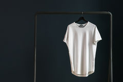 T-shirt with short sleeves on a hanger against the background of a dark wall. Stock Photos