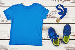 T-shirt, sneakers and medal. Distinction of sport achievements Stock Photography