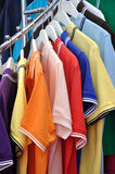 T-shirt in various color. T-shirt in various different color and same design, hanging on shelf for showing and sale Stock Photo