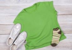 T-shirt verde em um fundo de madeira escuro foto de stock royalty free