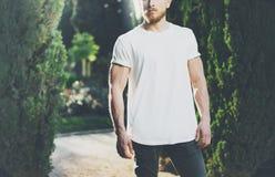 T-shirt vide blanc de port d'homme musculaire barbu de photo Effet extérieur de fond et de lumière du soleil de jardin vert horiz photo stock