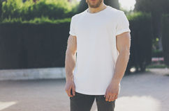 T-shirt vide blanc de port d'homme musculaire barbu de photo Fond extérieur de jardin vert brouillé maquette horizontale Images stock
