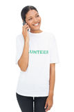 T-shirt volontaire de port modèle de sourire ayant un appel téléphonique Images stock