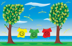T-shirts. Three t-shirts of different colours with smile on the clothes-line Stock Photo