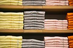 T-shirts avec des labels sur des étagères Photo libre de droits