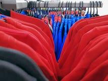 T-shirts en Polo Shirts Hanging op de Rekken met Selectieve Nadruk stock afbeeldingen