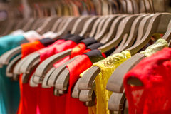 T-shirts hanging on a hanger in the store Stock Photos