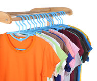 T-shirts hanging on hangers Stock Photos