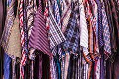 T-shirts hanging on hangers in thai market Stock Photo