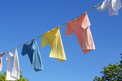 T-shirts hanging on rope in front of blue sky Royalty Free Stock Images