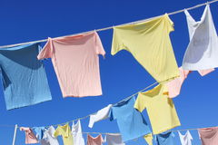 T-shirts hanging on rope in front of blue sky Stock Photo