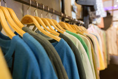 T-shirts hanging on wooden hangers. stock photo