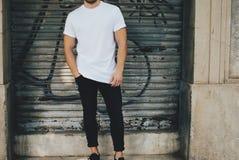 T-skjorta för vit för skäggig grabb bärande tom och svart jeans som står mitt emot garage Royaltyfria Bilder