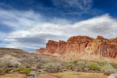 Capitol Reef National Park is in Utah`s southern desert. T surrounds a long wrinkle in the earth known as the Waterpocket Fold, with layers of golden sandstone stock image