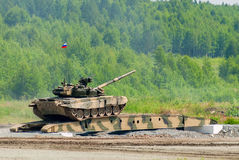 T-80 tank drives on bridge induced through. Nizhniy Tagil, Russia - July 12. 2008:  T-80 tank drives on bridge induced through obstacle. Display of military Royalty Free Stock Image