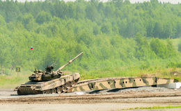 T-80 tank drives on bridge induced through obstacle. Nizhniy Tagil, Russia - July 12. 2008:  T-80 tank drives on bridge induced through obstacle. Display of Royalty Free Stock Photos