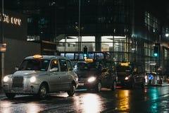 T?xis que esperam clientes em uma estrada em Canary Wharf, Londres, Reino Unido fotografia de stock