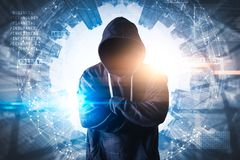 stock image of  the abstract image of the hacker standing overlay with futuristic hologram and the future cityscape is backdrop.