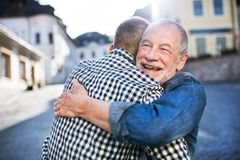 stock image of  an adult hipster son and his senior father in town, hugging.